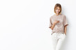 Stylish pretty young female with trendy hairdo, wears loose t-shirt and white trousers, types messages on smart phone, listens to her favourite track or audio book, isolated over white background