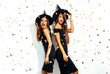portrait of two happy young women in black witch halloween costumes on party over white background. firecrackers in the background. confetti . the concept of Halloween . funny faces