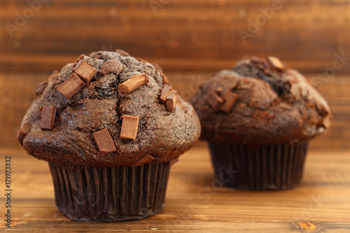 Chocolate chip muffins on wood in natural light Poster