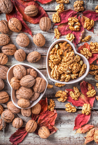 Papiers peints Orange eclat Overhead large group of walnuts in kernel and peel in heart shaped white ceramic jars on old rustic wooden table and red leaves in studio