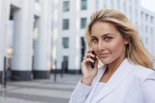 business woman talking on smart phone office worker street background © Alena Popova