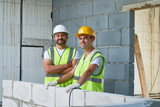 Group portrait of cheerful construction workers looking at camera with toothy smiles white taking short break from work, interior of unfinished building on background - 171986460