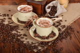 coffee with milk and chocolate foam in brown ceramic cups with vanilla and coffee grains