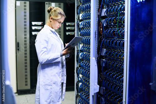 Side view portrait of young woman wearing lab coat  working with supercomputer inputting data to digital tablet standing by server cluster