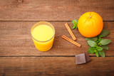 Freshly squeezed orange juice in a glass on a wooden background. Orange, melissa, cinnamon and chocolate with fruit juice. Space for text. View from above. - 172003075