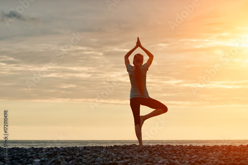 Girl at sunset practicing yoga at the seashore, back view