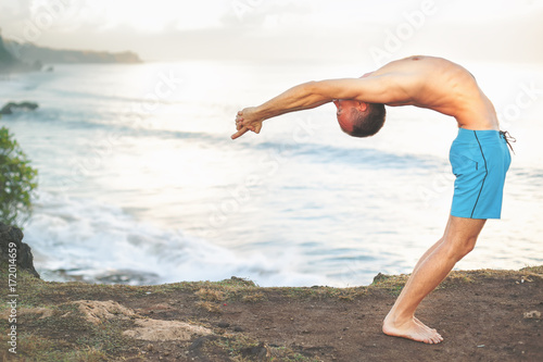 Deurstickers School de yoga Handsome man doing yoga at cliff with blue sea background