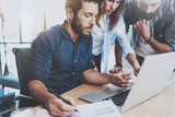 Group of coworkers sitting at the wooden table and working together in modern loft office.Horizontal.Blurred background.
