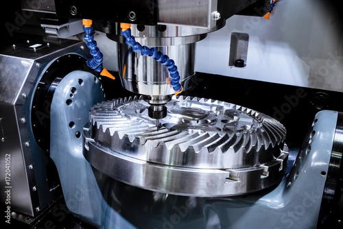 Leinwandbild Motiv A modern CNC milling machine makes a large cogwheel.