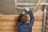 Worker installing insulation panels of mineral wool into roof of house. Roofing construction and thermal protection - 172045242