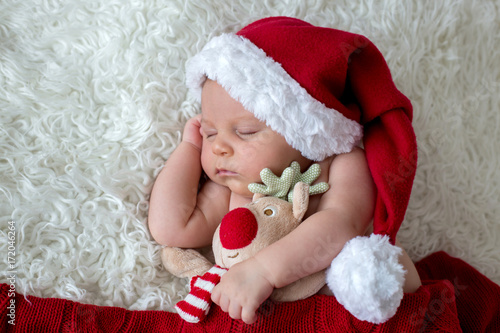 Little sleeping newborn baby boy, wearing Santa hat Poster