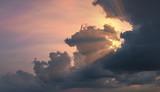 Sun rays shining through beautiful rain clouds at dusk. Dramatic cloudscape at sunset.