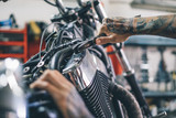 Fototapety Mechanic man repairs motorcycle