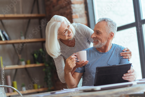 Positive aged wife giving a cup of tea to her husband