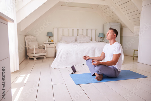 Papiers peints Ecole de Yoga Mature Man With Digital Tablet Using Meditation App In Bedroom