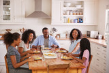 Fototapety Family With Teenage Children Eating Meal In Kitchen
