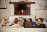 Family Sitting On Sofa In Lounge Next To Open Fire - 172077603