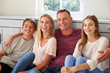 Portrait Of Smiling Family Relaxing On Seat At Home