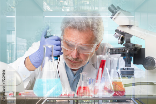 Senior life science research researching in modern scientific laboratory. Focused senior life science professional pipetting biological solution on microscope slide.