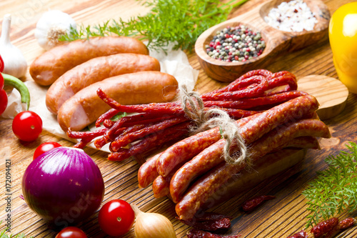 Fresh raw sausages with vegetables on wood - 172094421
