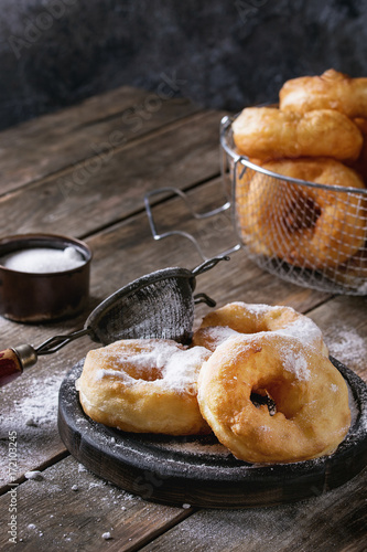 Homemade donuts with sugar powder on black serving board and in frying basket served with vintage sieve on old wooden plank table Poster