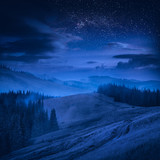 Mountain valley with blue clouds in a moonlight