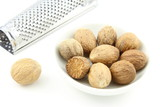 nutmeg seeds in a small white bowl - 172130088