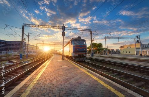 Wysoki prędkość pociąg pasażerski na torze szynowym przy zmierzchem w Europa. Stacja kolejowa z nowożytnym podmiejskim taborowym odjazdem, niebieskim niebem z chmurami i słońcem. Kolorowy krajobraz przemysłowy. Peron