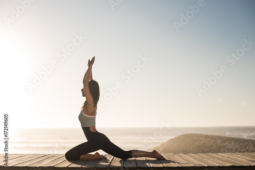 Fototapeta Fit woman enjoying sunset on the beach