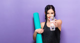 Happy young woman holding a yoga mat - 172154210
