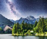 Majestic mountain lake in National Park High Tatra. Starry sky and Milky Way. Strbske pleso, Slovakia, Europe