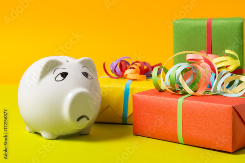 Piggy Bank with gift boxes, worried about money Poster