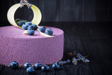 Delicious lavender cake with blueberries on black wooden table - 172176083