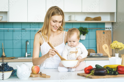 Young mother is cooking and playing with her baby daughter in a modern kitchen setting. Healthy food concept.