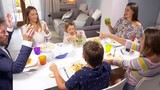 Happy large family celebrating and toasting at table slow motion - 172194246