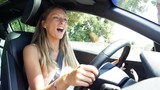 Happy blond woman smiling and  singing in car driving slow motion - 172199047