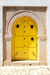 Vintage yellow door in Arabic style with a metal ornament.