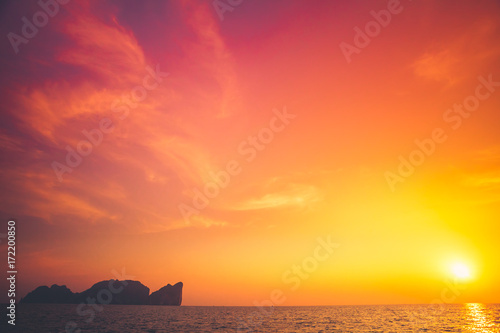 In de dag Koraal Beautiful tropical sunset in Krabi, Thailand. Dramatic and picturesque evening scene. Ocean and colorful orange cloudy sky in the background. Nature landscape. Travel background. Bright purple toning