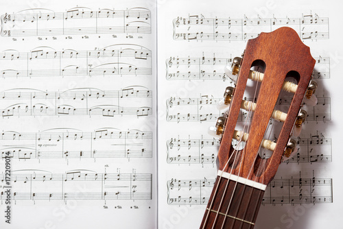 closeup of acoustic guitar on music notes Poster
