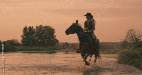 Slow motion 240fps shot of cowboy girl riding horse in water of sunset river