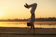 Young athletic men standing in yoga pose on near lake in the par