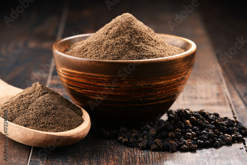 Composition with bowl of ground black pepper on wooden table - 172246463