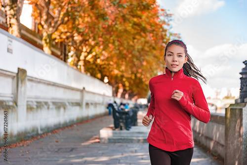 Poster Jogging Woman running in autumn fall outdoor city street. Female runner training outdoor in profile. Healthy lifestyle image of young Asian woman jogging outside. Fit ethnic Asian Caucasian fitness model.