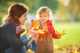 Little girl and her mother playing in the autumn park - 172291629