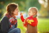 Little girl and her mother playing in the autumn park - 172291678