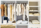 modern wooden wardrobe with clothes hanging on rail in walk in closet design interior - 172292853
