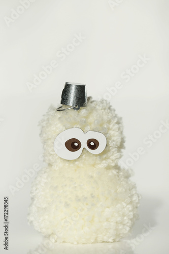 Snowman from white fluffy woolen pompoms  with  small bucket on his head on a light background Poster