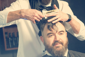 Stylist in black scarf and bow tie makes hair a man with a beard