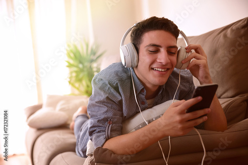Fototapeta Teen watching multimedia with headphones lying face down on couch