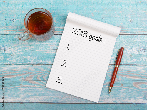 Notebook with new years goals for 2018 with a cup of thee and a pen on a blue wo Poster